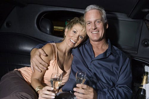 Couple in the back of a limousine enjoying a glass of wine