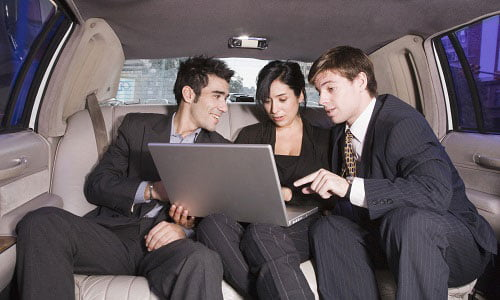 Business executives in the back of a limo sitting together reviewing a presentation on one of their laptops in preparation for a business conference.