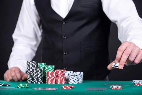 Casino dealer stacking chips on his black jack table