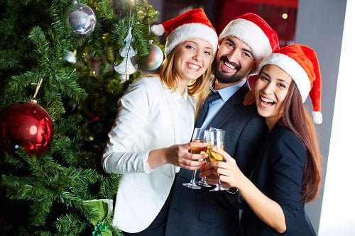 Work staff cheering drinks on a Christmas party while wearing Santa Claus hats