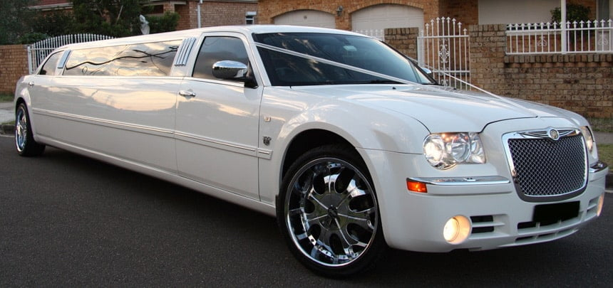 White stretch Chrysler limousine parked on the street
