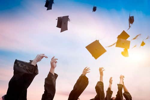 Graduates celebrating their graduation by throwing their hats into the air