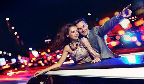 Couple in limousine standing up through the moon roof looking at the city.
