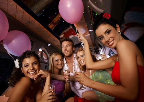 Group having a party with balloons and drinks in the back of a limo