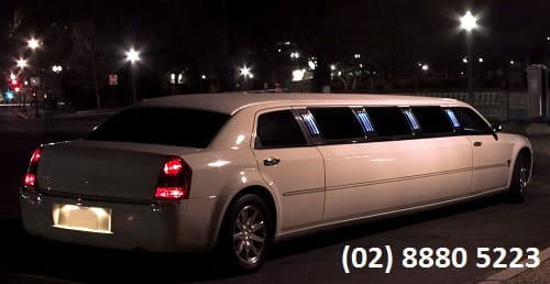 White Chrysler Stretch Limousine driving down road at night